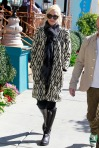 Singer Gwen Stefani ignores the unseasonable warmth of Los Angeles in a winter coat while at lunch with baby Zuma